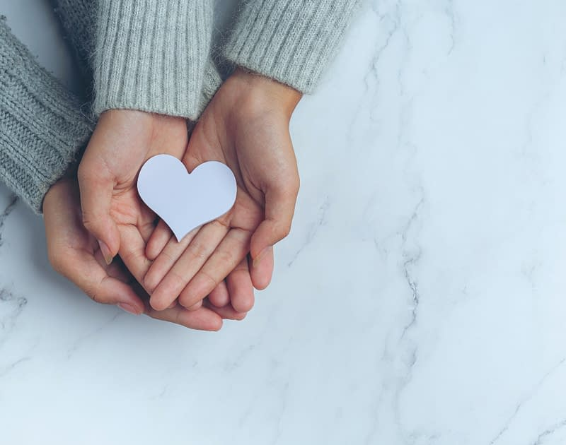 three hands holding paper heart
