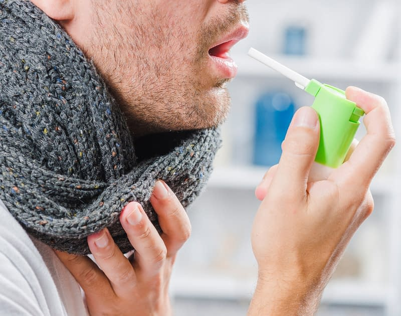 Man in scarf with sore throat spraying throat medicine