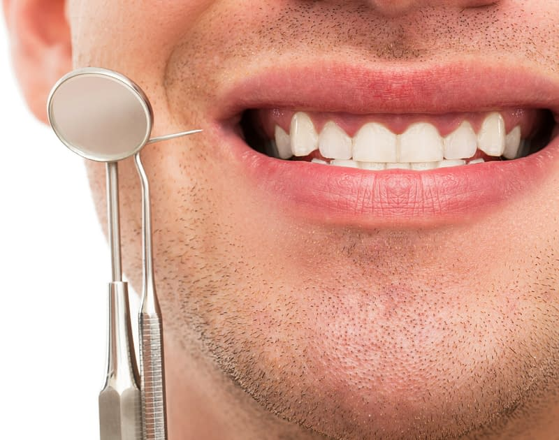 man smiling with dental tools