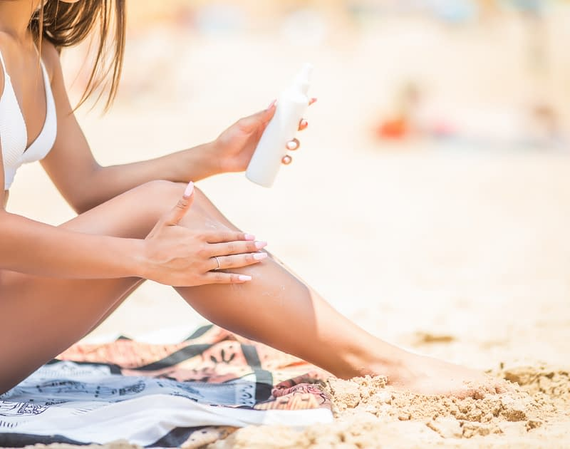 girl applying sun tan lotion on beach