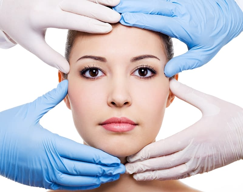 womans face with gloved hands examining